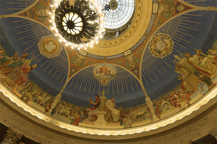 Rotunda with chandelier and skylight ringed with scenes of historical judges on thrones, interpreting laws for crowds.