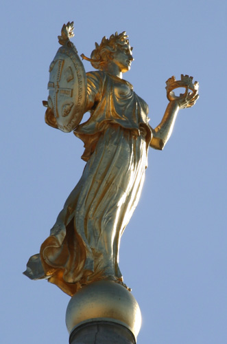 Golden goddess statue stands on top of dome