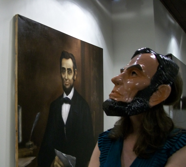 Person in Abraham Lincoln mask studies Abraham Lincoln painting