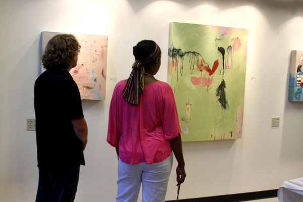 Two people study abstract paintings on gallery wall