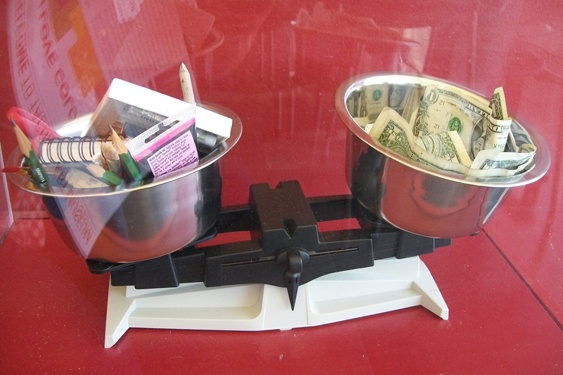 photo of donation box with a scale inside: art supplies on one side, dollar bills on the other