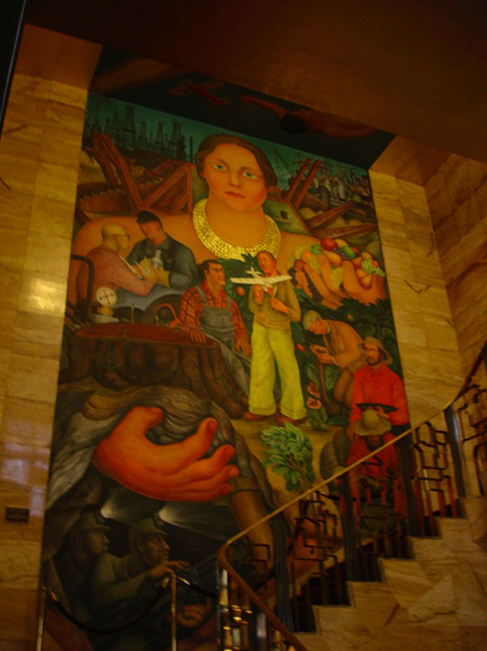 Large, vertical mural is the backdrop for a stairwell; the mural features figures, especially a large woman in the center.