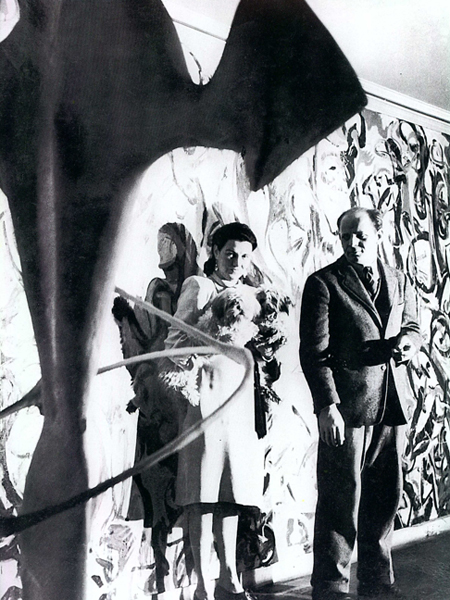 Framed by abstract sculpture, Peggy Guggenheim and Jackson Pollock stand in front of one of his paintings.