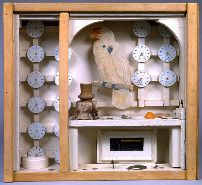 Glass-fronted box contains cockatoo and watches on display.