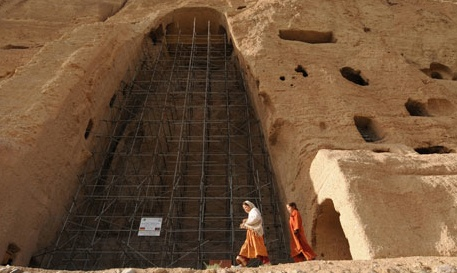 photo of two figures walking past scaffolded niche where Bamiyan monument used to stand