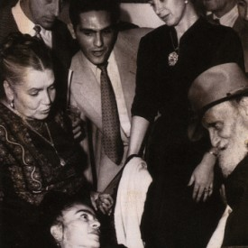 Well-wishers greet Frida in her bed at the opening of her first solo show in Mexico.