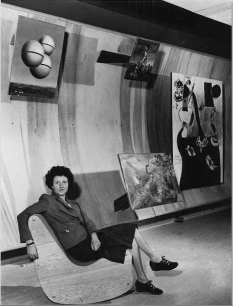 Confident Peggy Guggenheim reclines on modern rocking chair in sleek-looking art gallery with paintings on wall behind her.