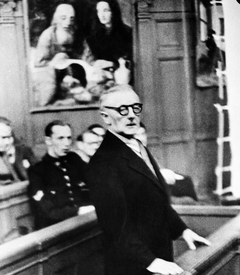 Han van Meegeren in the witness box at his trial. One of his forgeries is behind him.