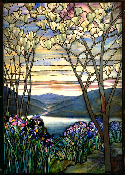 Stained glass window depicts flowering trees and irises on waterfront, with mountains behind and sky behind.
