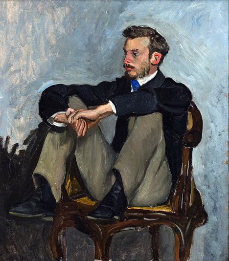 Earnest young Renoir dressed in a suit, seated on chair, with his feet drawn up and elbows resting on knees.