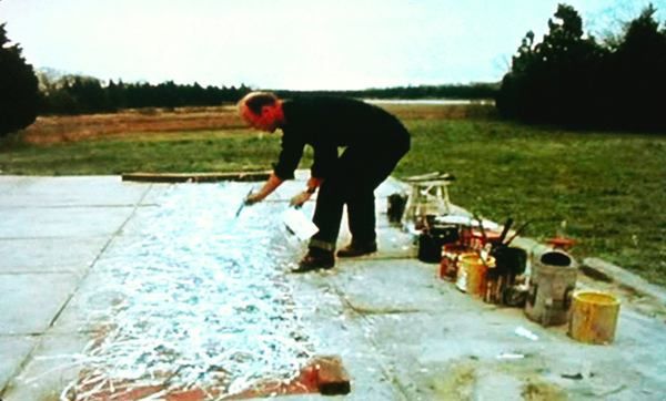 A man stands on a large canvas unrolled in a field, among paint cans, crouching and concentrating, holding a paintbrush