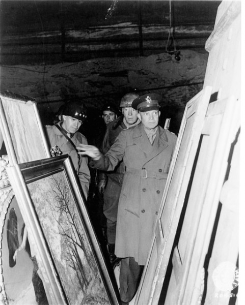 Dwight Eisenhower examining paintings in bunker in World War II.