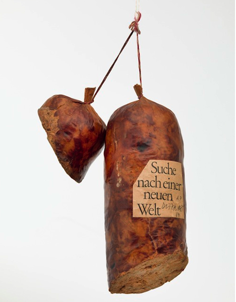 "Sausage-shaped ""meat"" cut in two pieces, hanging from string, with label in German."