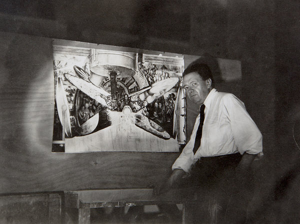 Diego Rivera poses next to small artwork.