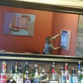 Seen from the mirror above Pimienta's bar, the artist hangs the show.