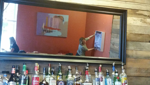 The painter, hanging artwork, is artistically reflected in mirror over a restaurant bar.