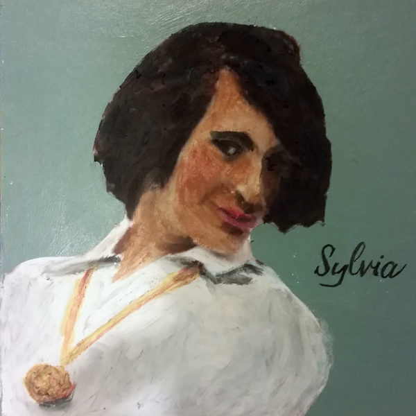 Sylvia, with large gold locket, coyly looks at viewer from underneath her bangs.