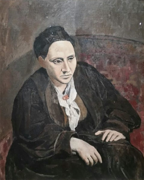 Gertrude Stein sits purposefully, leaning forward, hands in lap, and looks outward as though she is listening intently.