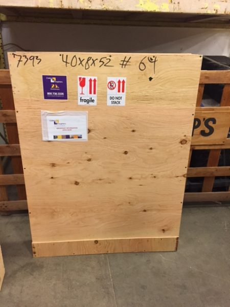 Large wooden crate with markings such as measurements, shipping instructions and labels in warehouse