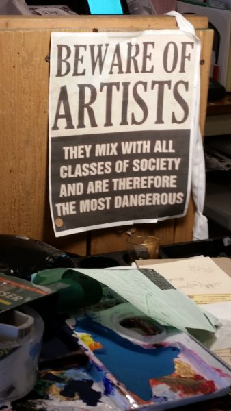 Humorous sign hanging above artist's table with palettes and papers