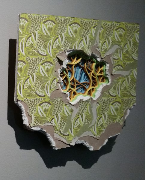 Fragment of wallpapered drywall, with hole in the center that reveals curlicued strips of colored paper inside