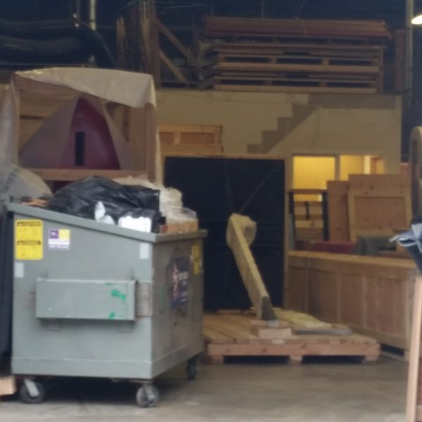Warehouse interior with palettes, dumpster, unknown structures