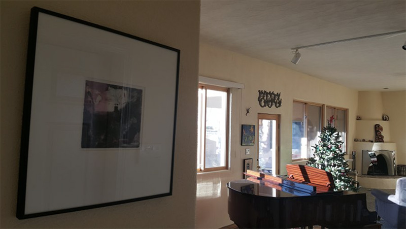 Framed abstract artwork hanging on wall of home with grand piano, Christmas tree and additional artwork in distance.