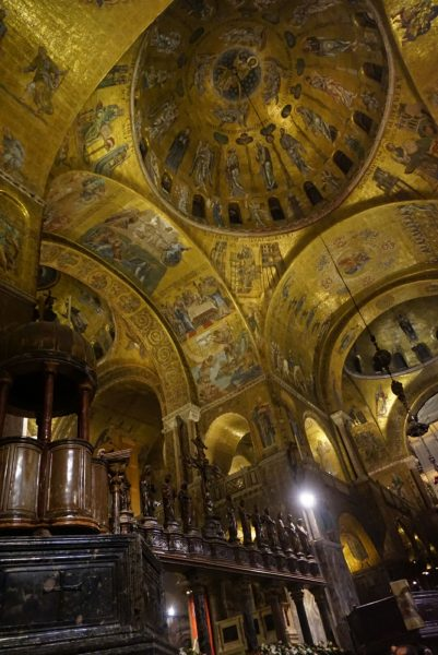 Interior of San Marco cathedral, focusing on shining gold mosaics decorating archways and domed areas of ceiling.