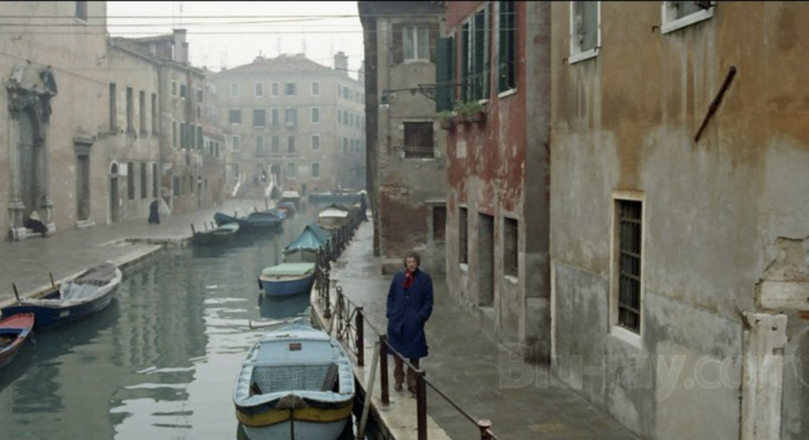 Man walking along Venice canal in winter with some mist and suggestion of dread