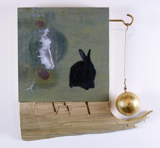 A black rabbit is placed among collaged papers, with a golden ball hanging from a wire, cradled by a piece of wood.