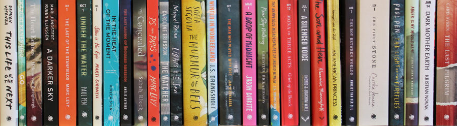 Colorful and varied types of books, lined up on a shelf.