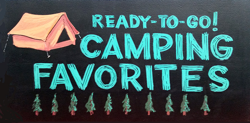 A hand-painted sign depicts a tent and a row of pine trees to advertise camping supplies.