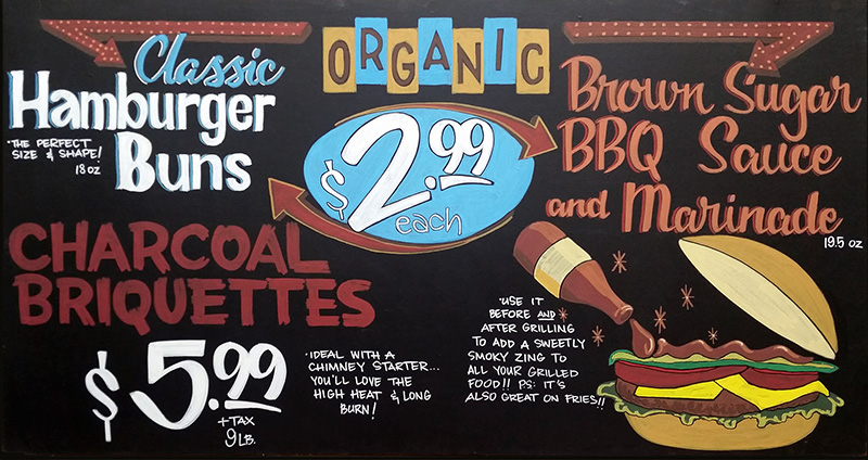A hand-painted sign uses a 1950s-style diner marquee and illustration of a burger to sell classic burger ingredients.