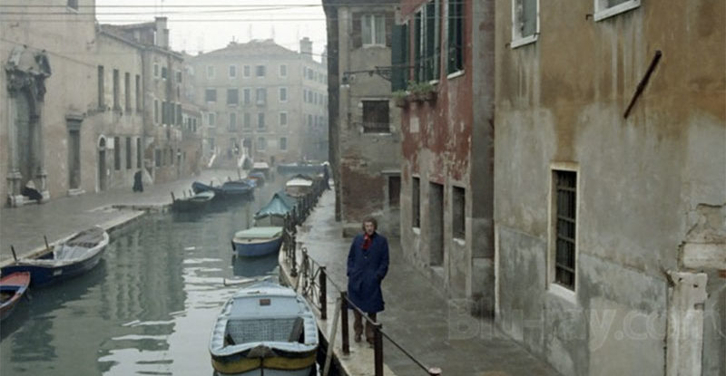 Man walking along Venice canal in winter with some mist and suggestion of dread.