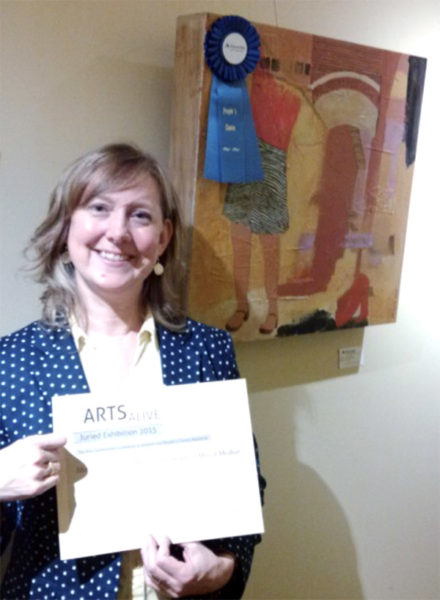 A smiling Maura McGurk holds certificate in front of blue ribbon-winning painting.