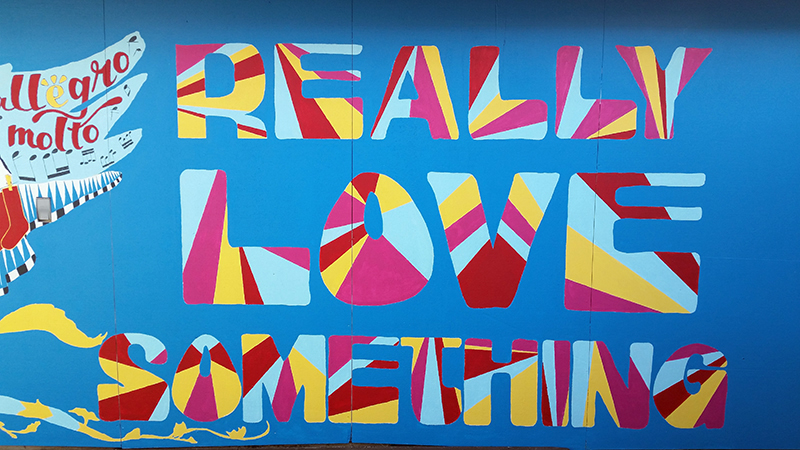 "A fragment of an outdoor mural depicts the words ""Really Love Something""."
